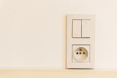 Light switch and socket on the wall Stock Photo