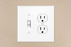 Light switch on wall. A brand new modern electrical toggle light switch and power outlet on a freshly painted wall royalty free stock image