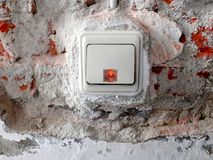 Light switch in a wall with removed plaster and visible bricks stock photos