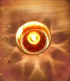 Light in table. Candle n shadow glass royalty free stock images