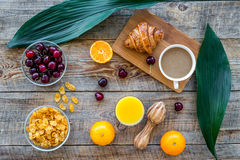 Light tasty breakfast. Muesli, oranges, cherry, french croissant and milky coffee on wooden table background top view Stock Image