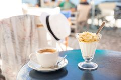 Light and tasty summer holidays breakfast cap of coffee cappuccino and yogurt with sliced banana, pear topped with honey in the stock photography