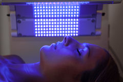 Light therapy session. A woman relaxes under a healing blue light therapy treatment Royalty Free Stock Images