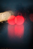 Light thru the window. Abstract red spots shot thru a rainy window royalty free stock image