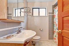 Light tones bathroom interior with grey tile wall trim. Floral patterned shower curtain and vanity cabinet with sink. Northwest, USA Royalty Free Stock Image