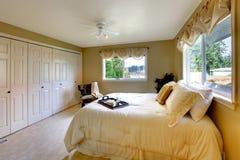 Light tones bedroom with a queen size bed. Beige carpet floor, walk-in closet stock photos