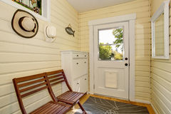 Light tones hallway with siding and exit to backyard. House interior. Light tones hallway with exit to backyard. Furnished with white cabinet and brown wooden Stock Images