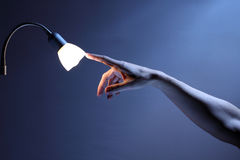 Light touch. Hand touching lamp with index finger, energy and environment concept Royalty Free Stock Photos