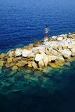 Light tower above rocks in the Aegean. Sailing to santorini in the aegean. the water is very clean under the rocks Royalty Free Stock Photos