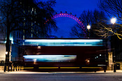 Light Trail of a Bus with London Eye. A red London bus passing by on an evening street scene sporting the London Eye in the background Royalty Free Stock Images