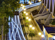 Light trail of cars on a city downtown with nobody on scene. Light trail of cars making the curve of a street of a city. View from above, sidewalk, post lights Stock Image