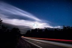 Light trail of a passing car on a rural road at night. Royalty Free Stock Images