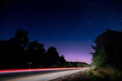 Light trail of a passing car on a rural road at night. Stock Photo