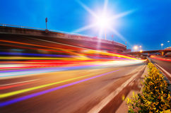 Light trails. High speed traffic and blurred light trails under the overpass at night scene Royalty Free Stock Image