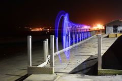 Light Trails and Beach at Night. Light trails at the board-walk, on the beach with lights from the pier and Sandown Bay, Isle of Wight, in the background Royalty Free Stock Photography