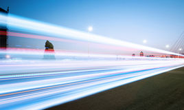 Light trails. Cars light trails on the modern bridge at dusk stock photography