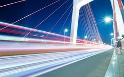 Light trails. Cars light trails on the modern bridge at dusk royalty free stock photos
