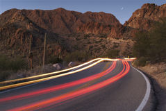 Light trails on a desert road. Light trails from cars on a desert road at Gates Pass, Tucson, AZ Royalty Free Stock Images