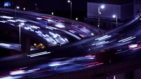 The light trails of fast moving cars on overpass,city traffic,time lapse. Aerial freeway busy city rush hour heavy traffic jam highway Shanghai at night,time stock footage