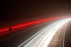 Light trails on a foggy motorway. Long exposure photo of traffic on the move at night on a motorway. M40 motorway in Warwickshire, England, on a foggy evening royalty free stock photo