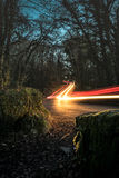 Light trails through the forest. Long exposure image of car light trails and commuters travel across Dartmoor National Park at night Stock Image