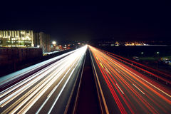 Light trails on highway with a industry building - slightly toned. Stock Image