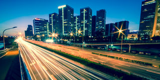 Light trails on the modern city at dusk Royalty Free Stock Image