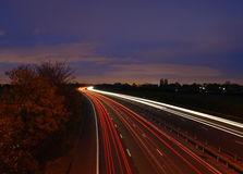 Light trails on motorway at dusk. Light trails of cars on suburban motorway at dusk Royalty Free Stock Image