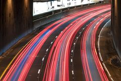 Light trails on a motorway. Long exposure of a motorway traffic at night - light trails painted in the shot with a subway station in the background stock images