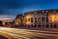 Light trails pass the Colosseum in Rome at dusk Royalty Free Stock Images