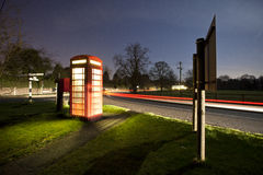 Light trails on a rural road, with phone box Royalty Free Stock Photography