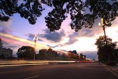 Light trails on the urban street at twilight Stock Photos