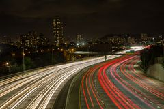 Light trails on the Kapiolani exit to the motorway. Light trails of vehicles on the Kapiolani exit to the motorway looking towards lights of Waikiki, Oahu royalty free stock images