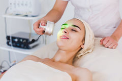 Light treatment in spa clinic. Young healthy woman with good skin doing cosmetic procedures in spa clinic. Light treatment Royalty Free Stock Image