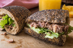 Light Tuna Fish Sandwich with orange juice in a poppy seeds bread. Royalty Free Stock Photo