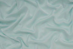 Light turquoise satin material, blue sateen fabric, silk textile. Beautiful creative background royalty free stock images