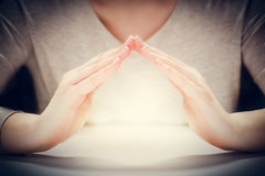 Light under woman's hands in gesture of protection, care. Stock Images