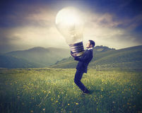 Light up. Businessman lighting up a green meadow with a light bulb Stock Images