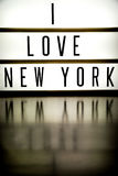 A light up board displaying the phrase I LOVE NEW YORK. A light up board displays the phrase I LOVE NEW YORK reflected on wood stock photography