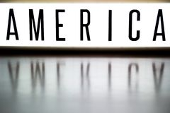 A light up board displays the phrase AMERICA. Reflected on wood Stock Photo