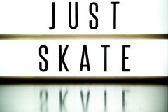 A light up board displays the phrase JUST SKATE. Reflected on wood Stock Photos