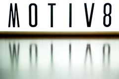 A light up board displays the phrase MOTIV8. Reflected on wood Royalty Free Stock Image