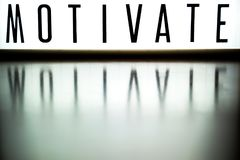 A light up board displays the phrase MOTIVATE. Reflected on wood Royalty Free Stock Image