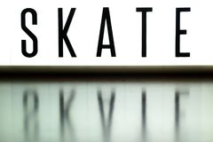 A light up board displays the phrase SKATE. Reflected on wood Stock Image