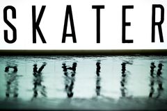 A light up board displays the phrase SKATER. Reflected on wet slate Royalty Free Stock Photos