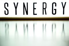 A light up board displays the phrase SYNERGY on wood. A light up board displays the phrase SYNERGY reflected on wood Royalty Free Stock Images