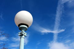 Light up the sky. Round ball street light against a blue sky with cloud wisps Stock Photo