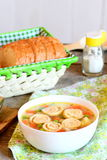 Light vegetable soup with omelet in a bowl, bread slices on a basket. Soup with omelet, carrot, peas, leek, cauliflower and potato Royalty Free Stock Images
