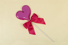 Light violet lollipop with red sateen bow. Light violet heart shaped lollipop with red sateen bow on light yellow background with slight shimmer royalty free stock image