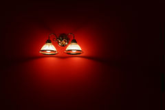 Light on the wall. Lamp in the red wall Stock Photos